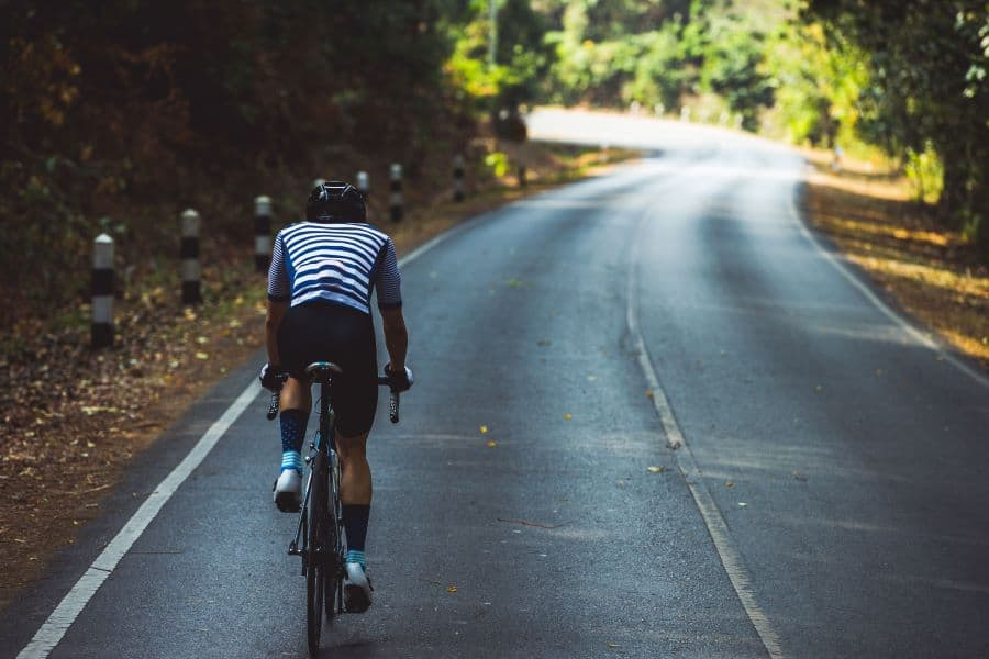 man cycling on road bike on road