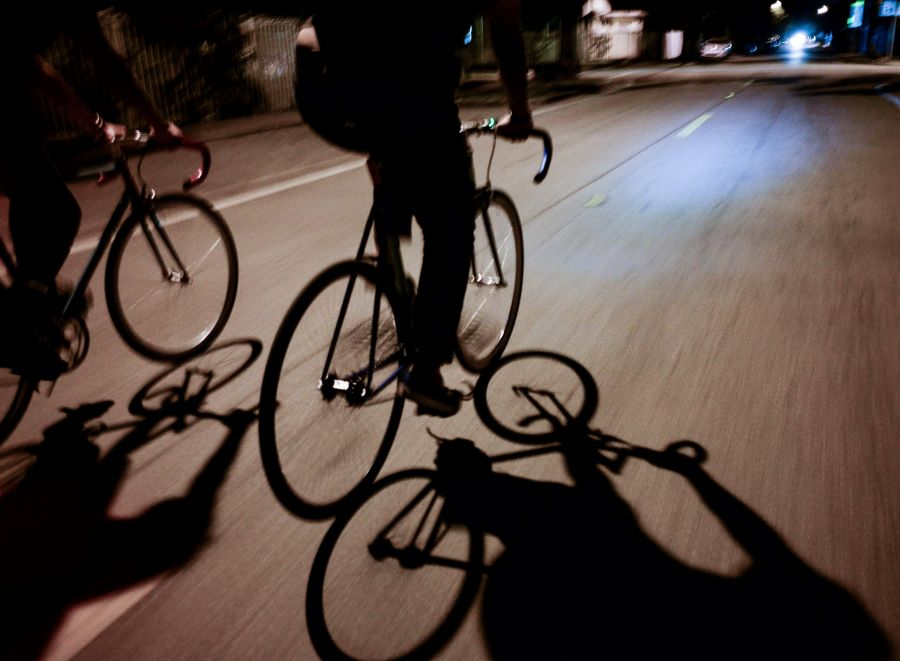 Two cyclists cycling down a road at night