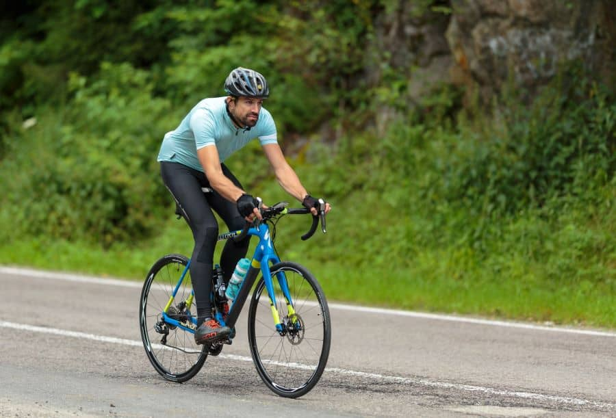 Cyclist on road bike going down hill on road
