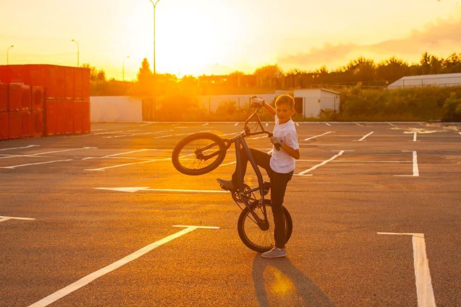 Kid in parking lot doing a stationary wheelie on bike