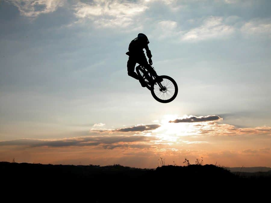 Kid jumping on bike with sunset behind