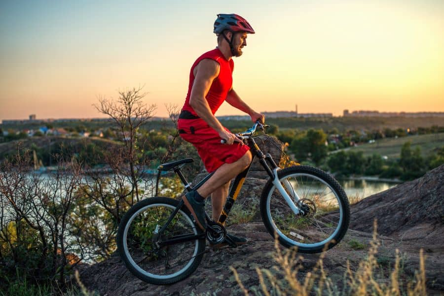 Mountain bike rider riding on dirt track at sunset