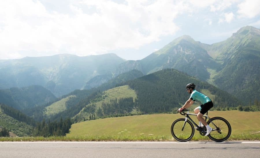 Road biker riding on road in mountains