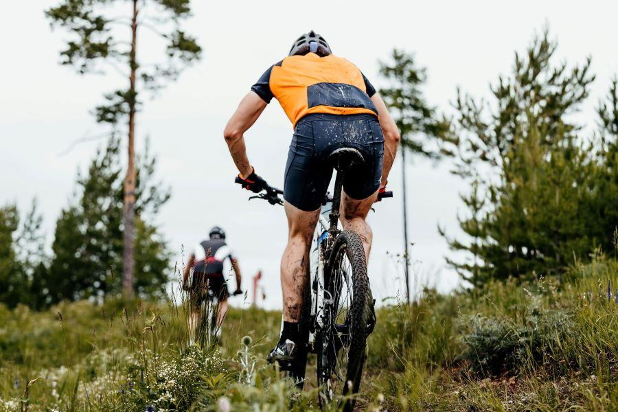 Mountain biker going up a muddy trail on a hill