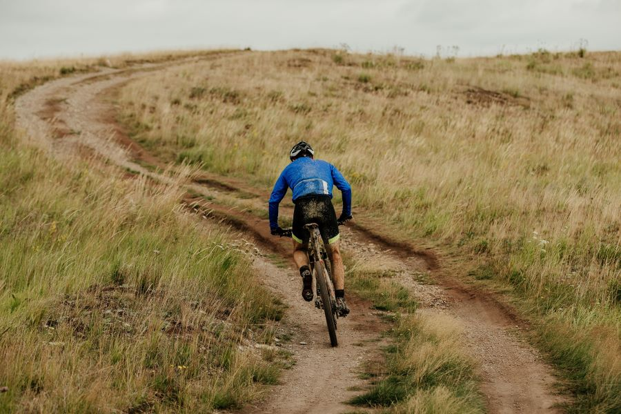 Mountain biker going up a dirt track on a hill