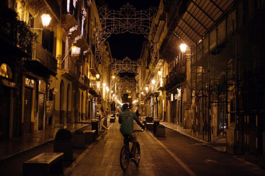 Man cycling through the city at night