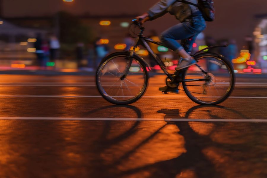 Cycling through the city at night with bright lights in backdrop