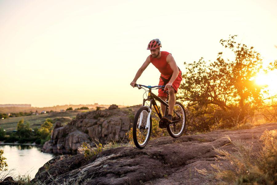 Mountain biker going down a dirt hill