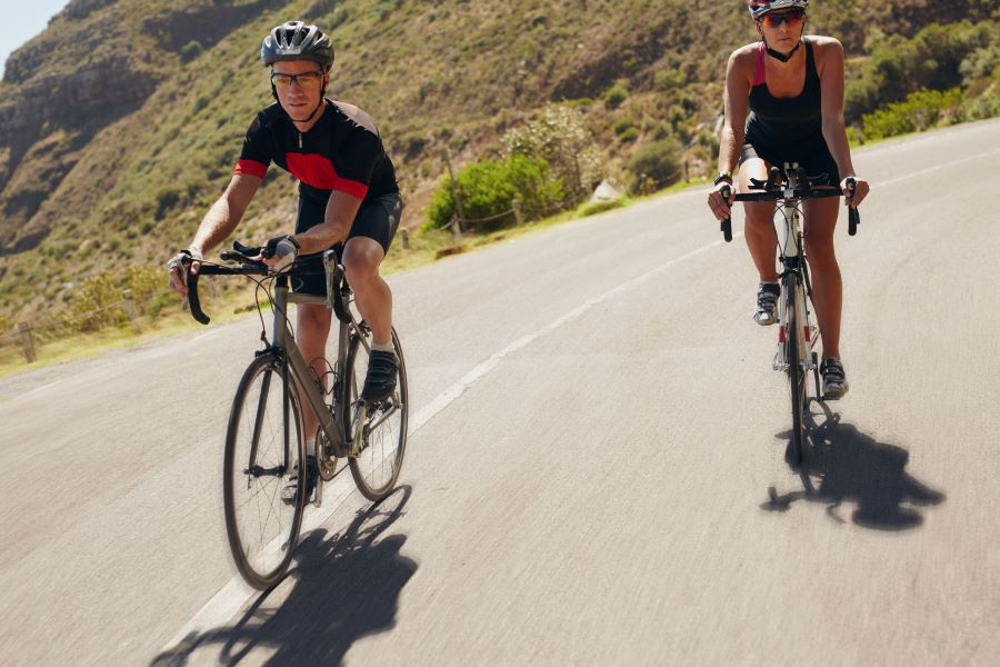Two cyclists on road bikes going downhill